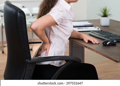 Close-up Of Young Businesswoman On Chair Having Backpain In Office