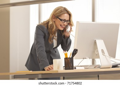 Close-up of young businesswoman on the phone while looking at computer