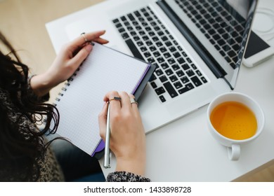 Closeup of a young businesswoman sitting at the table at home in front of laptop, making notes in the notepad. Cup of hot tea and a smartphone beside.