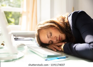 Close-up Of A Young Businesswoman Sleeping Over Desk