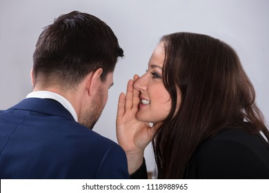Close-up Of Young Businesswoman Whispering Into Male Partner's Ear