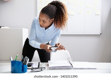 Close-up Of A Young Businesswoman's Hand Taking Photo Of Document On Mobilephone Secretly In Office