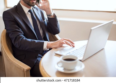 Closeup of a young busy businessman with a beard doing some work on a laptop and making some call on a cell phone