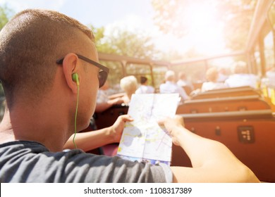 closeup of a young cacausian man traveling on an open top tour bus, checking a city map and wearing earphones, with a sunbeam in the background