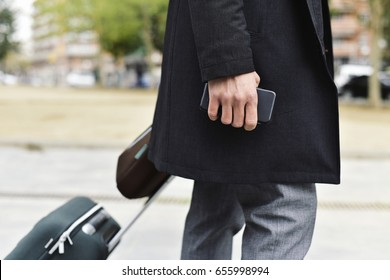 closeup of a young caucasian businessman in a gray suit and a dark gray coat pulling a trolley while is carrying a brown briefcase in one hand and a smartphone in the other hand, on the street
