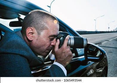 closeup of a young caucasian detective or paparazzi man, in a gray suit, taking photos from inside a car