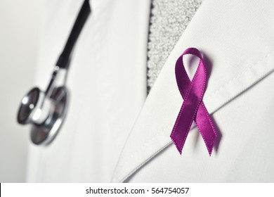 closeup of a young caucasian doctor with a purple ribbon pinned in the flap of his white coat