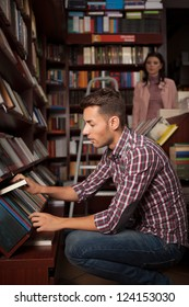 close-up of young caucasian handsome guy in bookstore choosing a book from a lower shelf