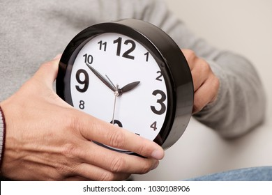 closeup of a young caucasian man adjusting the time of a clock