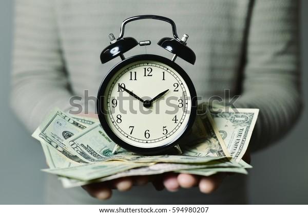 目覚まし時計と多くの米ドル紙幣を手にした白人の若い男性の接写で、時間はお金だと思う