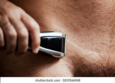 closeup of a young caucasian man in the bathroom trimming the hair of his pubes with an electric trimmer