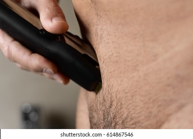 closeup of a young caucasian man in the bathroom trimming the hair of his pubis with an electric trimmer