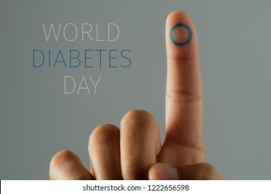 closeup of a young caucasian man with a blue circle, symbol of the diabetes, in his forefinger, and the text world diabetes day