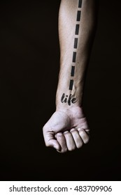 closeup of a young caucasian man with a dashed line and the word life simulating a tattoo in his forearm, against a black background