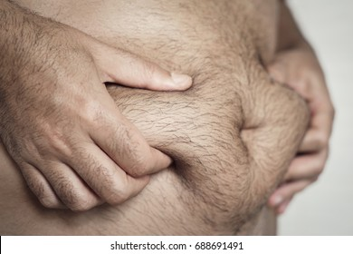 closeup of a young caucasian man grabbing the fat of his hairy stomach