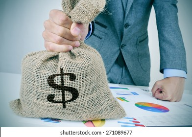 closeup of a young caucasian man in a grey suit with a money bag on a desk full of different charts