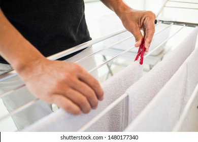 closeup of a young caucasian man hanging wet clothes on a drying rack in a balcony