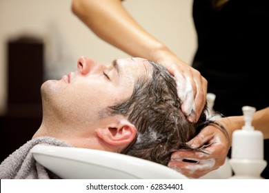 Close-up of a young caucasian man having his hair washed in a hairdressing salon