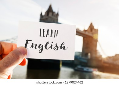 closeup of a young caucasian man holding a signboard with the text learn English written in it, in front of the Tower Bridge in London, United Kingdom