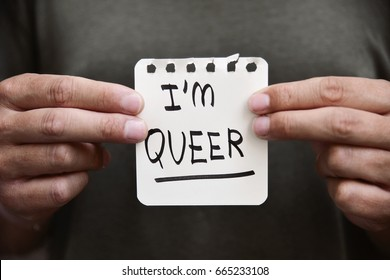 closeup of a young caucasian man holding a paper note in front of him with the text I am queer written in it