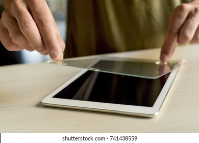closeup of a young caucasian man installing a screen protector in a digital tablet