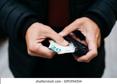 closeup of a young caucasian man on the street putting in or taking off euro banknotes from his wallet