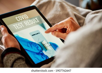closeup of a young caucasian man in pajamas, sitting on a sofa wraped in a gray blanket, checking the result of his covid test in a simulated app in his smartphone, that reads covid test result