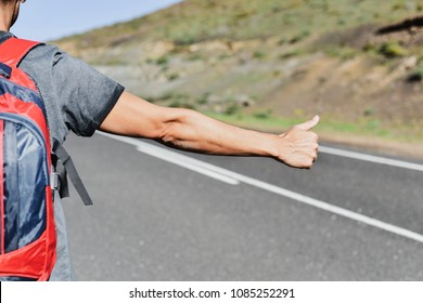 closeup of a young caucasian man, seen from behind, carrying a backpack hitchhiking in a secondary road, with his thumb up