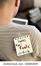 closeup of a young caucasian man seen from behind using his tablet, with a note with the text happy april fools day attached with tape to his back