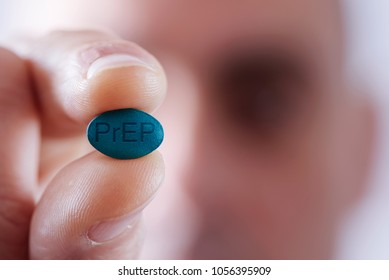 closeup of a young caucasian man with a simulated PrEP pill in his hand