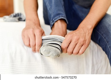 closeup of a young caucasian man sitting on the edge of the bed putting on or taking off a pair of striped socks