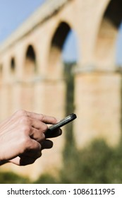 closeup of a young caucasian man with a smartphone in front of the roman aqueduct Pont del Diable in Tarragona, Spain