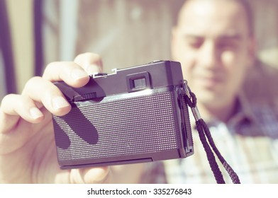 closeup of a young caucasian man taking a selfie with an old film camera, in a urban scenery, with a filter effect