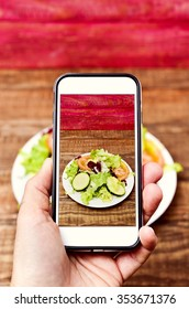 closeup of a young caucasian man taking a picture with his smartphone of a plate with salad placed on a wooden table