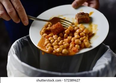 gros plan d'un jeune homme caucasien jetant le reste d'une assiette de ragoût de pois chiche dans la poubelle