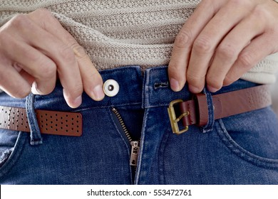 closeup of a young caucasian man trying to fasten his trousers, after his weight gain