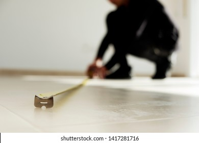 closeup of a young caucasian man using a measuring tape on a beige tiled floor