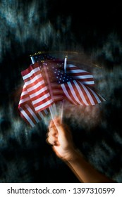 closeup of a young caucasian man waving some american flags, against a dark gray background