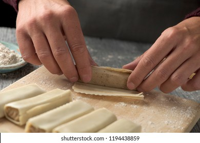 closeup of a young caucasian man, wearing a gray apron, preparing some meat stuffed cannelloni on a rustic wooden table