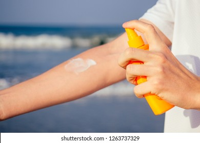 closeup of a young caucasian man wearing a white T-shirt applying sunscreen to his body against the sea ocean