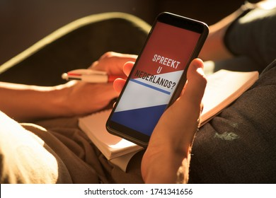 closeup of a young caucasian man, wearing casual clothes, sitting on an armchair, having his smartphone in his hands with the text do you speak Dutch and the flag of the Netherlands in its screen