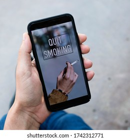 closeup of a young caucasian man, wearing casual clothes, outdoors having his smartphone in his hands with the text quit smoking in its screen