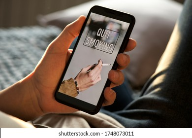 closeup of a young caucasian man, wearing casual clothes, lying on bed, having his smartphone in his hands with the text quit smoking in its screen