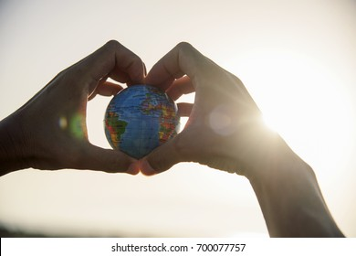 closeup of a young caucasian man with a world globe in his hands forming a heart against the sky and a ray of sun showing up on the right