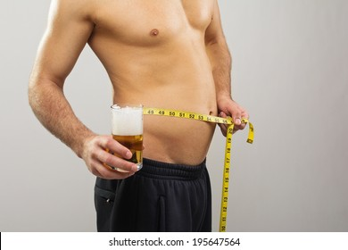 Closeup of young Caucasian man's stomach. Man is holding a glass of beer and tape measure. Dieting and alcohol concept.