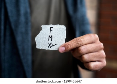 closeup of a young caucasian person holding a piece of paper with the letters F for female, M for male and X for the third gender category, written in it, with a check mark on the X