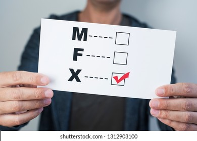 closeup of a young caucasian person holding a form with the letters M for male, F for female and X for the third gender category, written in it, with a check mark on the X