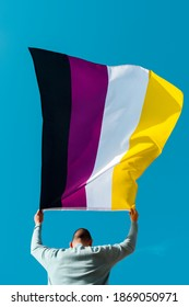 closeup of a young caucasian person, seen from behind, waving a non-binary pride flag on the air