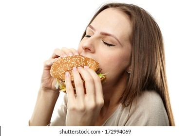 Closeup of a young caucasian woman eating a big hamburger, isolated on white background