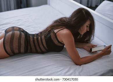 closeup of a young caucasian woman face down in bed using a smartphone